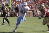Former North Carolina quarterback Mitchell Trubisky (10) stiff arms a Florida State defender in 2016.