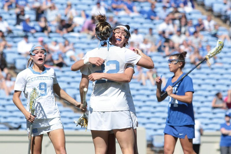 Seniors Marie McCool (4) and Maggie Bill (22) embrace after a goal against Duke on April 21 at Kenan Stadium.