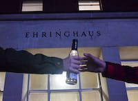 In a photo illustration, two students pass a bottle of alcohol back and forth in front of Ehringhaus Residence Hall. Seven of Ehringhaus' 18 resident advisers were fired from the residence hall this semester.