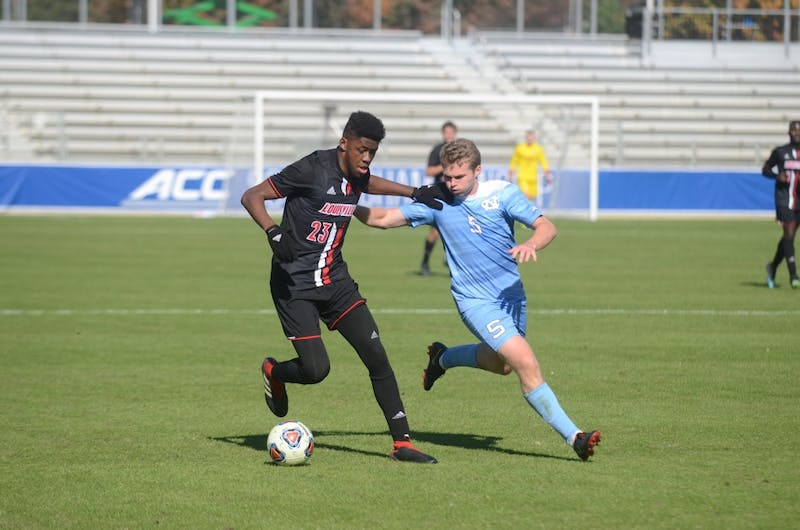 Defender John Nelson (5) fights Louisville forward Izaiah Jennings (23) for the ball during Sunday's ACC Championship game at WakeMed Soccer Park. UNC lost to Louisville 1-0.