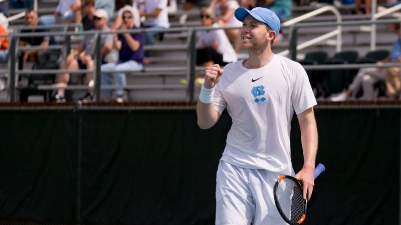 Sophomore Simon Soendergaard celebrates during an Sunday, April 1, 2018 match against Virginia at the Cone-Kenfield Tennis Center.
