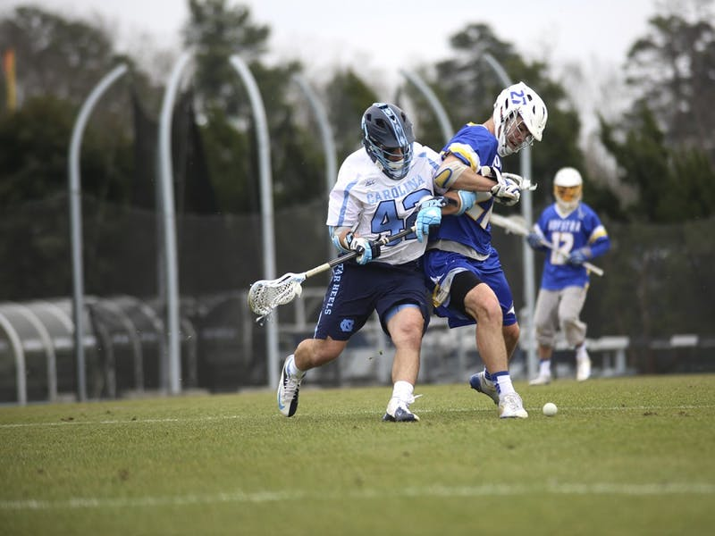 Tar Heel midfielder Peyton Klawinski (42) fights for a loose ball in Saturday's match against Hofstra. UNC fell 10-5.