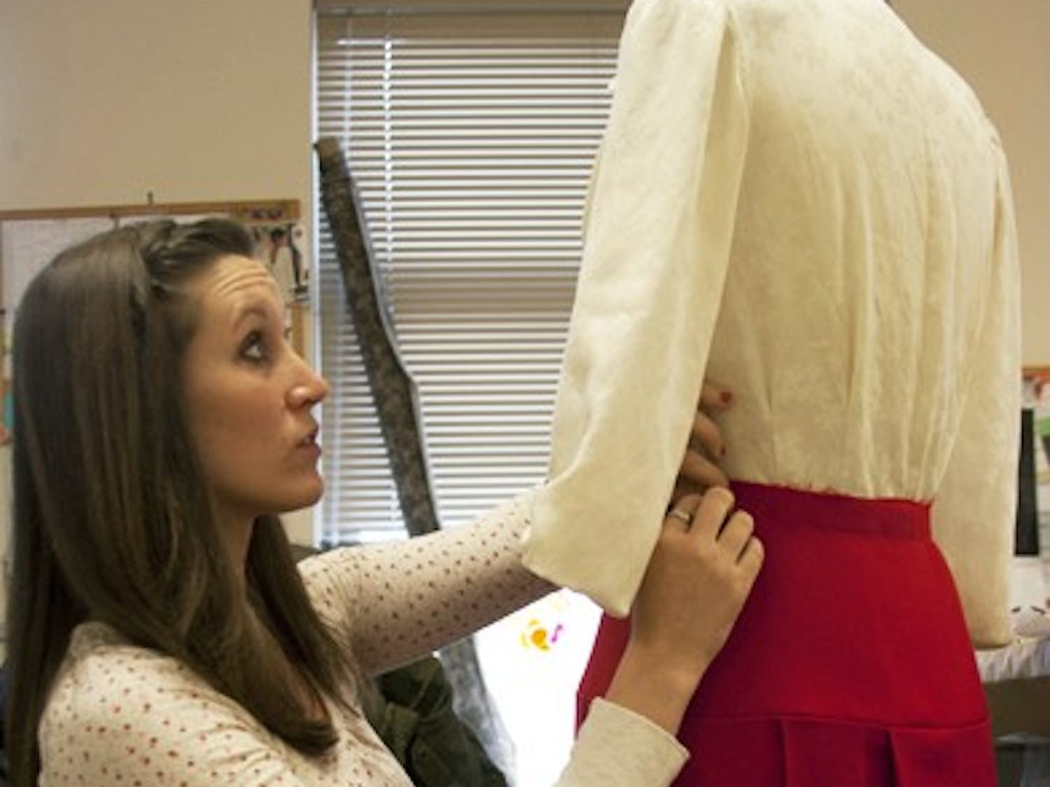 Kelly Renko, a second-year graduate student in the UNC costume production program, adjusts the costume of the Mary Hatch Bailey character.