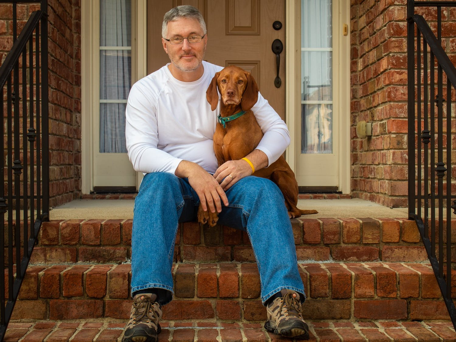 Jeff Nash, retiring CHCCS spokesperson, sits on the steps outside of his Apex home with his dog, Darby.