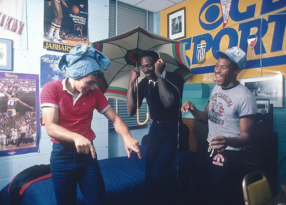 <p>UNC junior Michael Jordan (middle) and two friends laugh together in Jordan's dorm room in Granville Towers in 1983. Photo courtesy of Lane Stewart.</p>