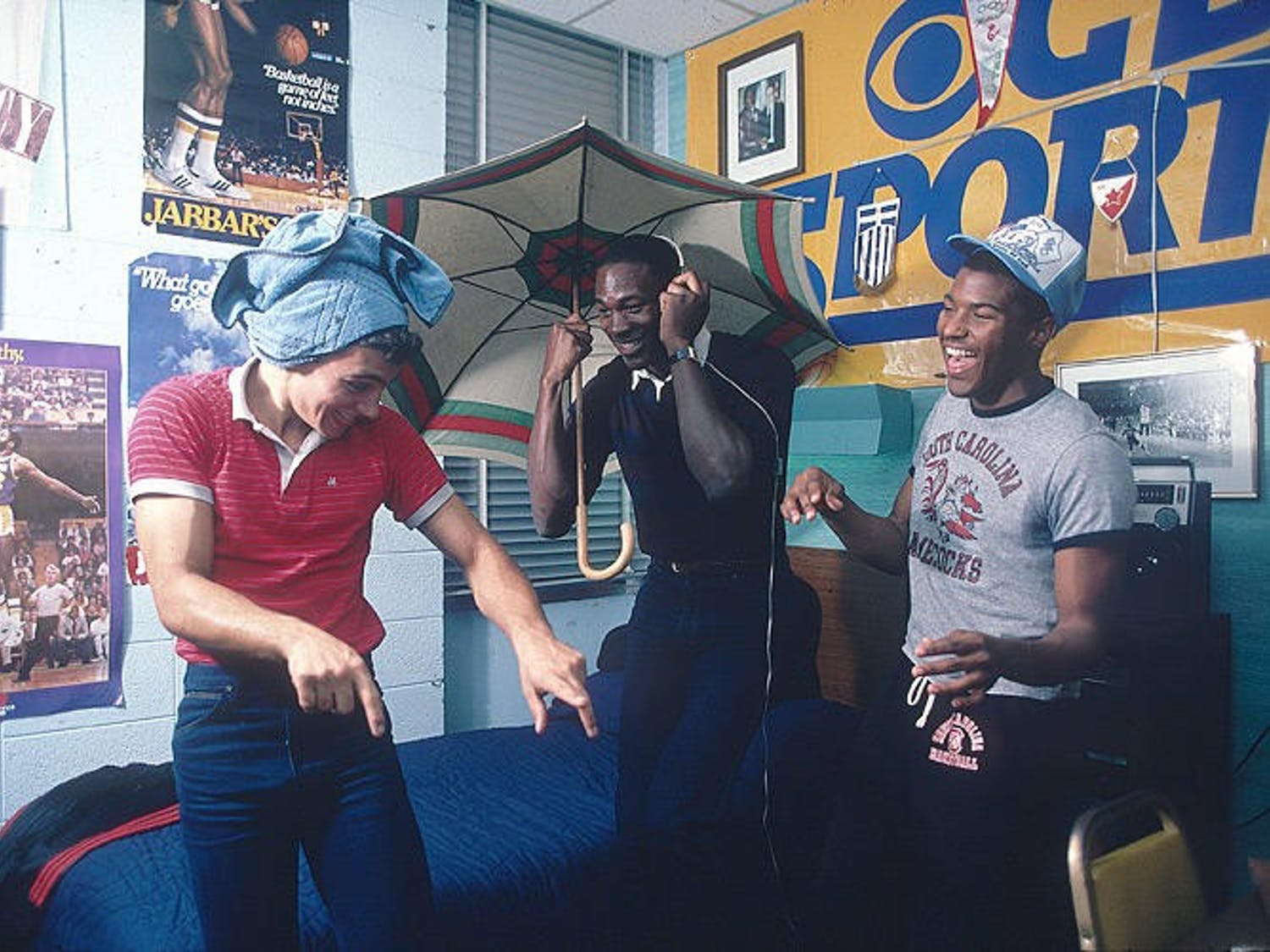 UNC junior Michael Jordan (middle) and two friends laugh together in Jordan's dorm room in Granville Towers in 1983. Photo courtesy of Lane Stewart.