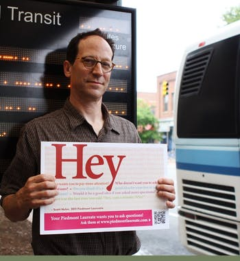 Scott Huler, the 2011 Piedmont Laureate, holds one of the new bus  placards he hopes will get people thinking about about various issues.
