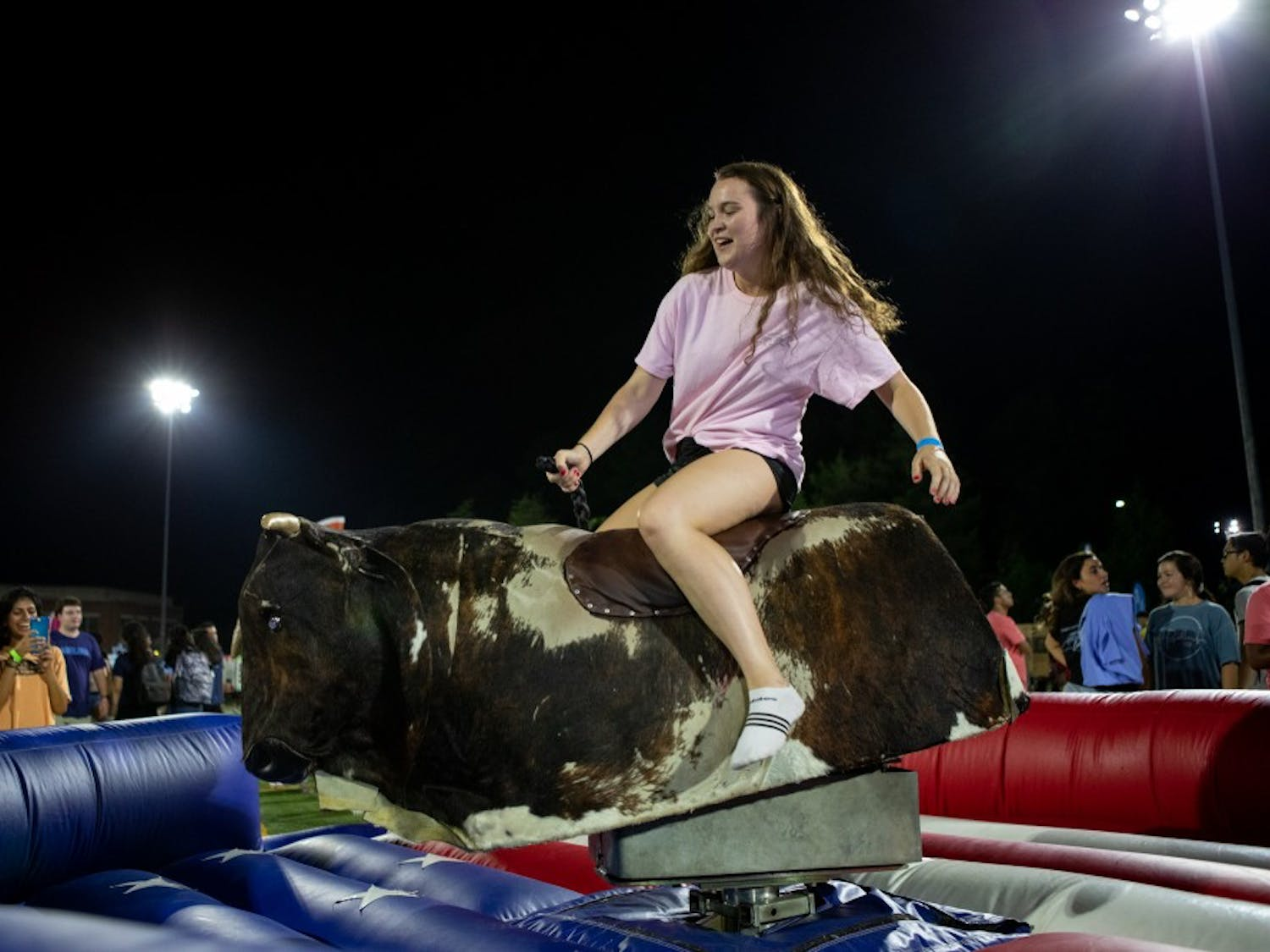 Catriona Dick, a junior psychology major, rides the mechanical bull during Fallfest on Hooker Fields on the evening of Sunday, August 18 2019.