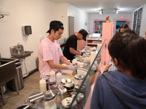 Employees Andy Chen (left) and Kevin Mendenoza (right) make rolled ice cream for customers on Tuesday, Sept. 25 at the newly-opened Ice Lab, located at 405 W. Franklin Street in Chapel Hill, North Carolina.