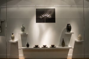 Ceramic works by Becca Kenney displayed below a photograph by Xiaoyin Chen. Photo by Jubal Strube