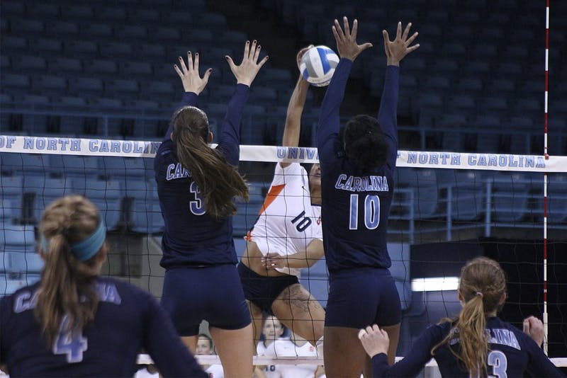 Beth Nordhorn and Chaniel Nelson attempt to block a spike during Sunday afternoon's win over Syracuse.