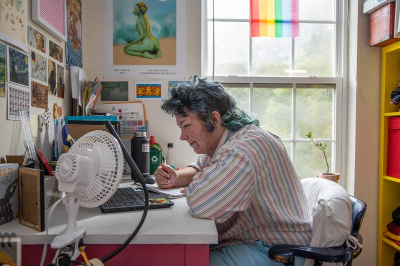 Sophomore SamLevi Sizemore completes his German homework in his Chapel Hill apartment on Thursday, Sept. 10, 2020. As a studio art and English double major, Sizemore has filled his workspace with posters, plants, and flags to make his apartment feel like home.