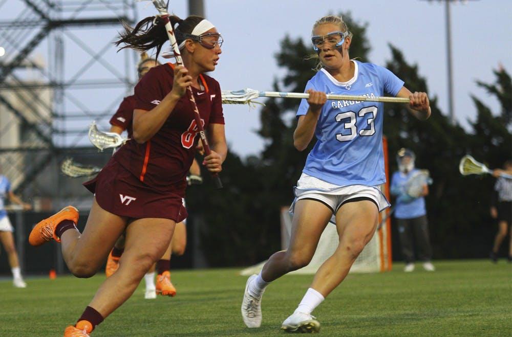 Maggie Auslander (33) defends against Amanda Uliano (8) of Virginia Tech. The Tar Heels won 15-6 Wednesday evening.