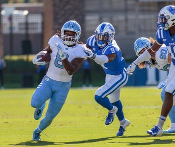 UNC sophomore running back Michael Carter runs past a Duke defender during North Carolina's 42-35 loss to the Blue Devils at Wallace Wade Stadium on Nov. 10.