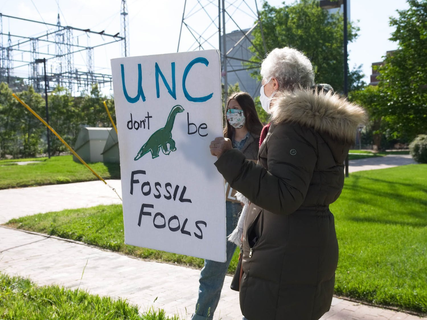 Amelia Covington and Judith Lechner hold up signs outside of UNC's coal plant on Friday, Apr. 23, 2021.