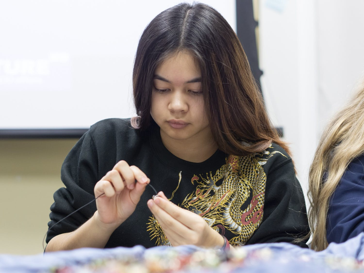 Makeila Cox, first-year biology major, makes a bracelet out of beads at the Carolina for Amani general body meeting at Campus Y, Jan. 29, 2020. The bracelets are sold once a month in the Pit to raise money for The Amani Children's Foundation  which funds New Life Home Orphanages in Kenya.