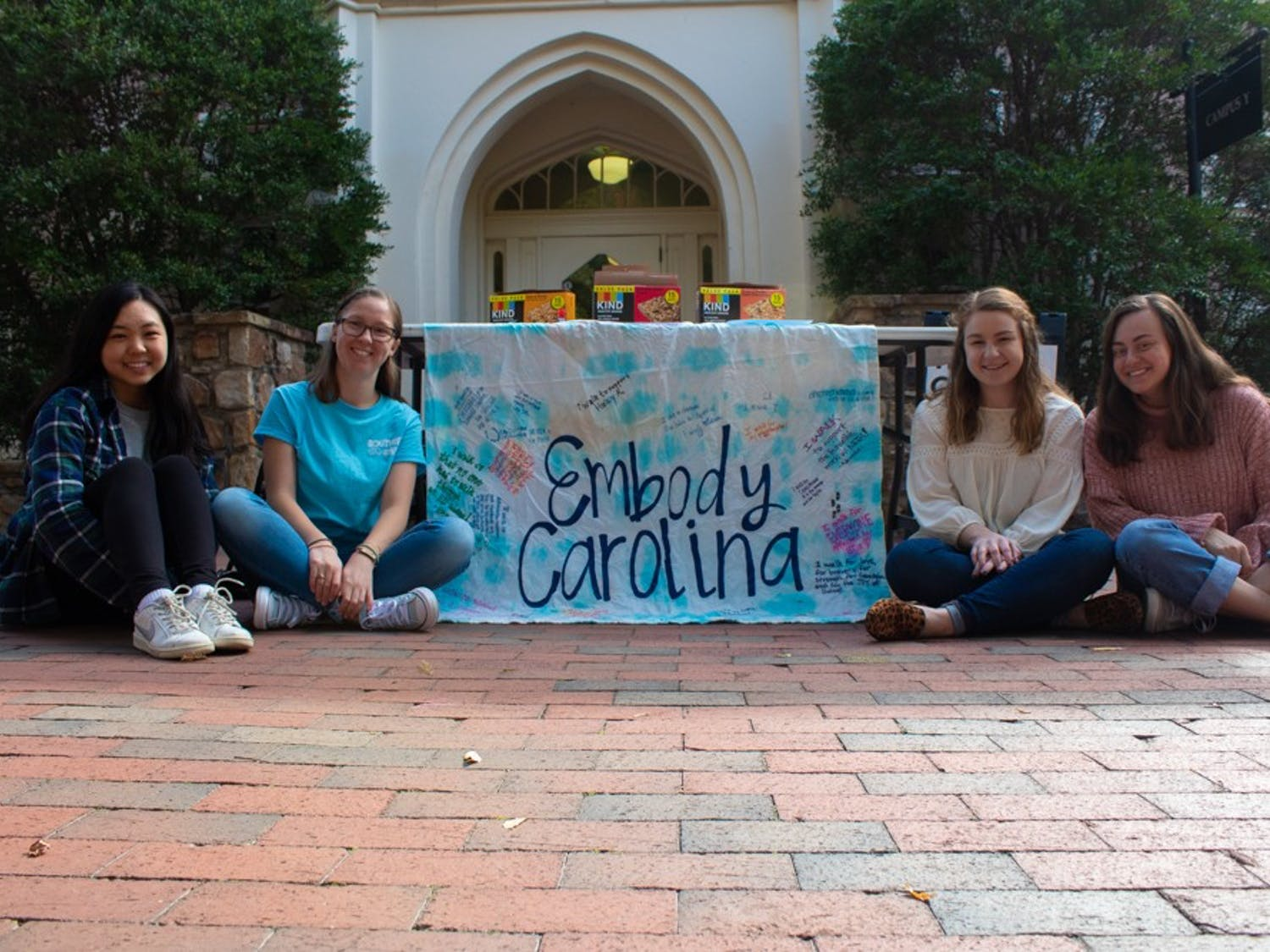 (From left ) Grace He, a junior music and psychology major; Cameron Lynch, a sophomore undecided major; Ashley Broadwater, a senior public relations major; and Maya Wahl, a junior exercise and sport science major, pose in front of an Embody Carolina banner in front of the Campus Y on Monday, Nov. 4, 2019.