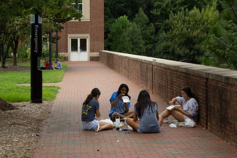 A group of UNC students eat lunch outside of Chase Dining Hall on Thursday, Aug. 13, 2020. With stricter dining options due to COVID-19, students have found alternative ways to eat together.