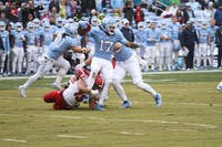 Junior wide receiver Anthony Ratliff-Williams (17) hangs onto the ball while safety Stephen Morrison (13) grabs his legs during the game against NC State on Saturday, Nov. 24, 2018. UNC lost 34-28 in overtime, ending their season 2-9.