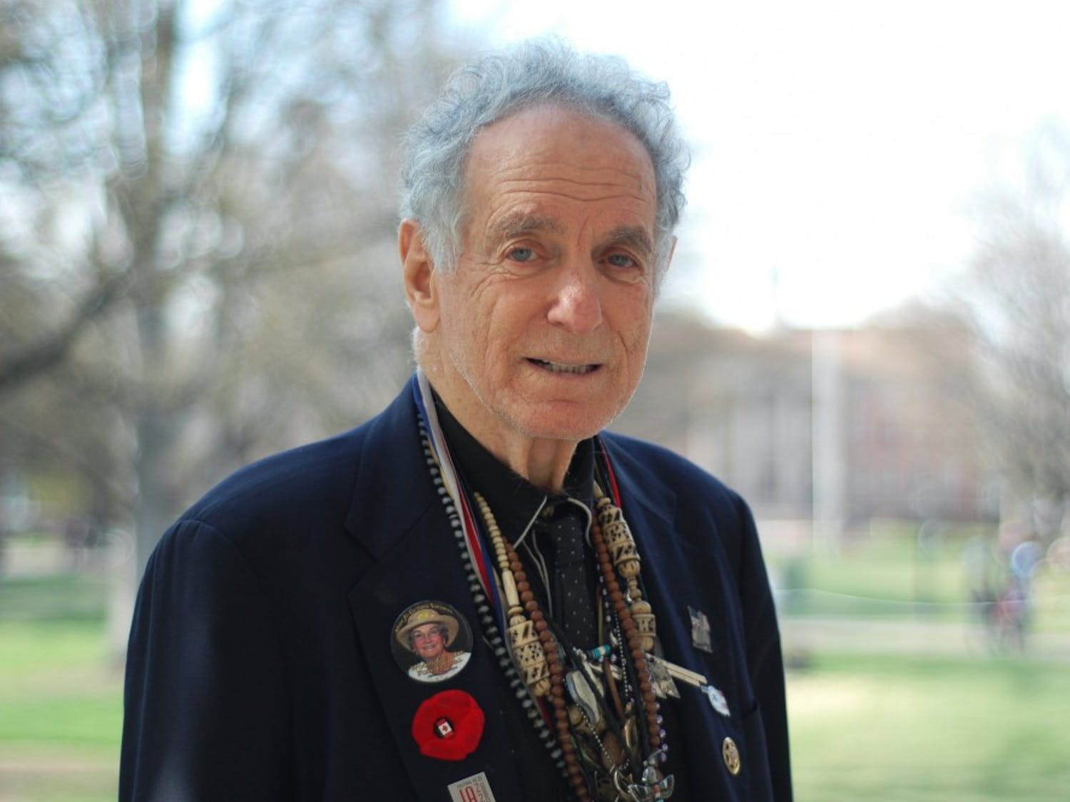 David Amram stands with a necklace made by his daughter from assorted trinkets and collectibles he has be given and found over the years. Amram has spent his life doing many types of things, most notably his musical career with multiple instruments.