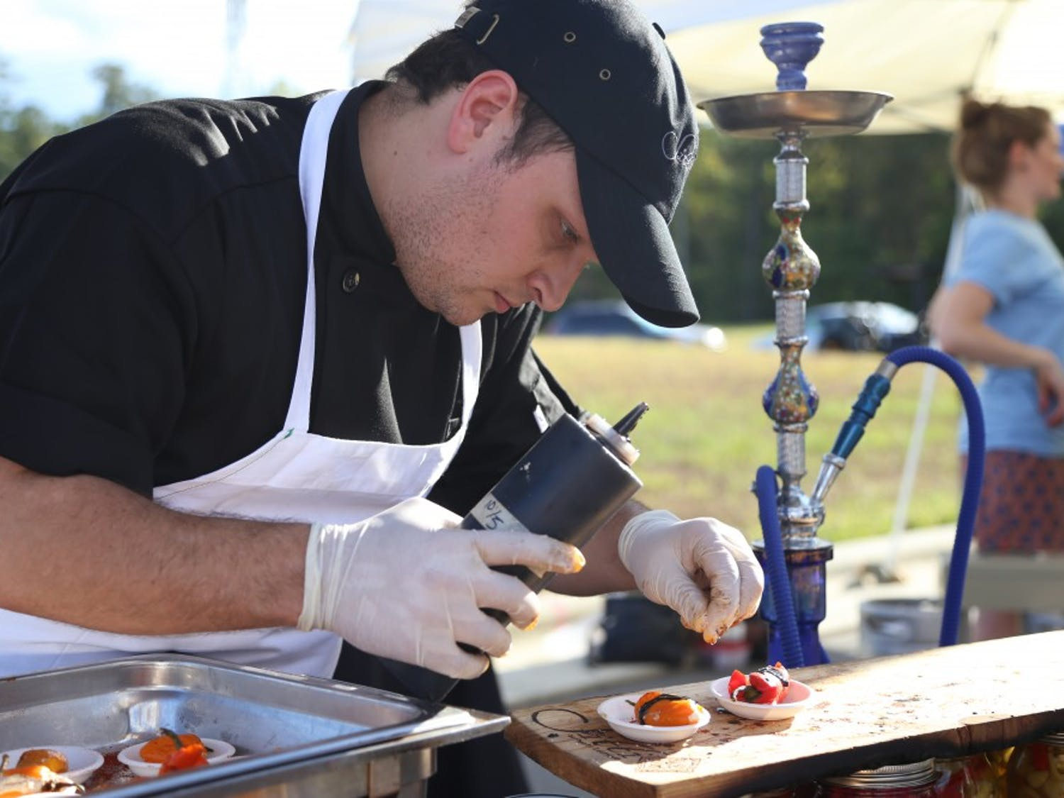 Patrick Ewald, the general manager of Sitti Restaurant in Raleigh, prepares a sample of mini sweet bell peppers stuffed with goat cheese and topped with a pomegranate balsamic vinaigrette. 