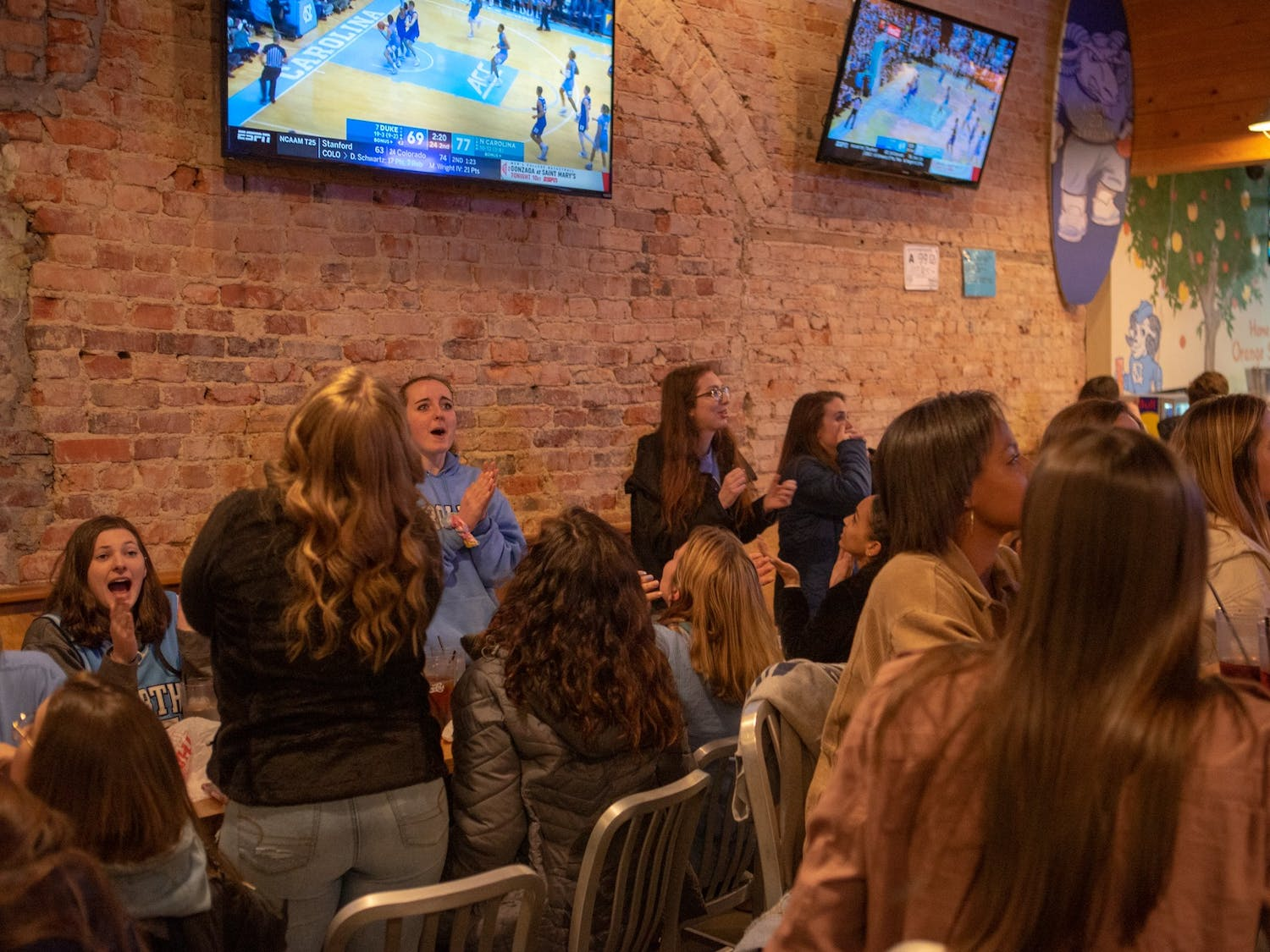 Spectators in Sup Dogs on Franklin Street cheer during UNC's game against Duke as the Tar Heels hold an 8-point lead in the second half on Sat. 8, 2020. The Tar Heels lost to Duke 98-96 in overtime.
