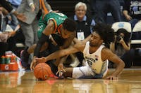 Miami guard Chris Lykes (0) and UNC first-year guard Coby White (2) fight for the ball on Saturday, Feb. 9, 2019 in the Smith Center. UNC men's basketball defeated Miami 88-85 in overtime.