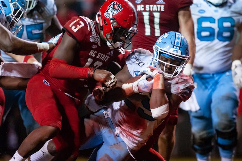 N.C. State sophomore Tyler Baker-Williams (13) tackles UNC's sophomore running back Javonte Williams (25) in the endzone during a game at Carter-Finley Stadium on Saturday, Nov. 30, 2019. UNC beat State 41-10, the first time since 2015.