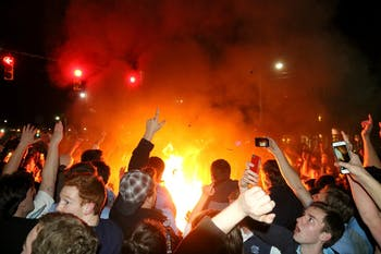 Students and Carolina basketball fans rush Franklin St. after defeating Duke. The students set bonfires to jump over.