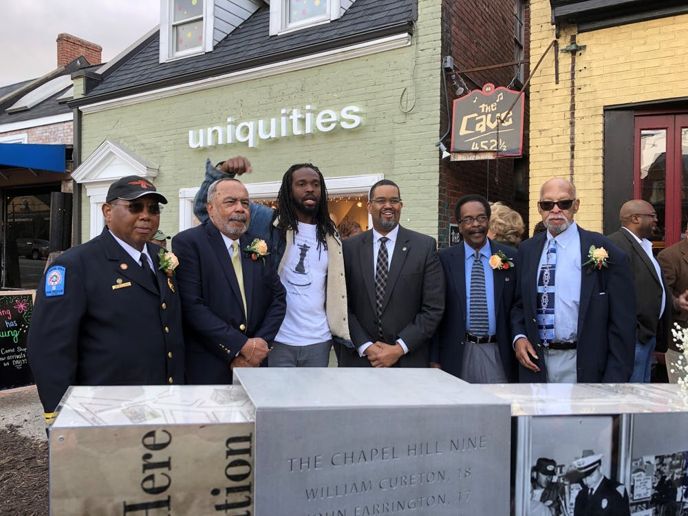 <p>(From left) Surviving Chapel Hill Nine members Albert Williams and James Merritt, marker artist Steven Hayes, Chapel Hill Town Manager Maurice Jones, and two other Chapel Hill Nine members Dave Mason Jr. and 'Clyde' Douglas Perry stand behind the new marker on Franklin Street. The marker was dedicated on Friday, Feb. 28, 2020.</p>