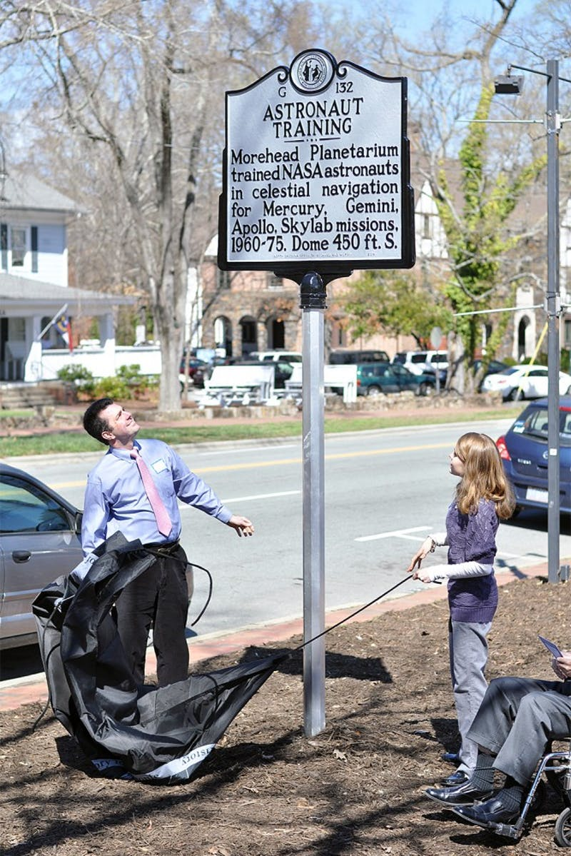 """Jarrod Jenzano, grandson of former astronaut educator Anthony Jenzano, and Gabi Tesoro, granddaughter of former astronaut educator Richard Knapp, unveiled the NC Highway Historical Marker G-132, """"Astronaut Training,"""" at the dedication ceremony outside of the Morehead Planetarium and Science Center on Wednesday."""