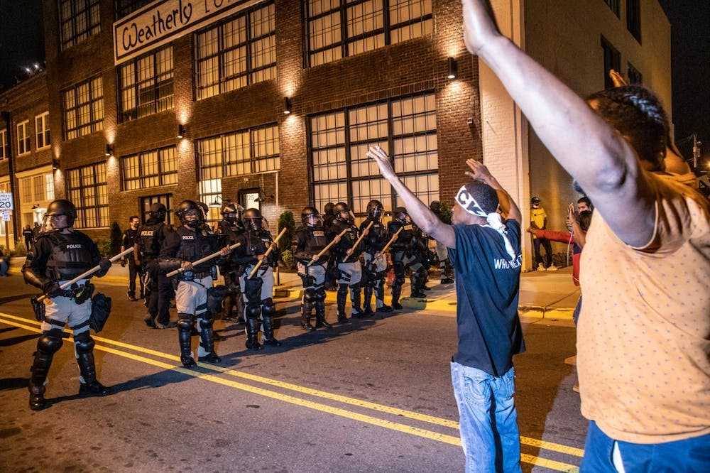 A demonstrator protesting the police killing of Andrew Brown Jr. raise their hands in front of a police line Tuesday, April 27, 2021, in downtown Elizabeth City. At least six protesters were arrested when police in riot gear marched toward roughly a dozen protesters two hours past curfew. Protesters were peaceful but refused to clear the streets. Photo courtesy of Travis Long/News & Observer/TNS