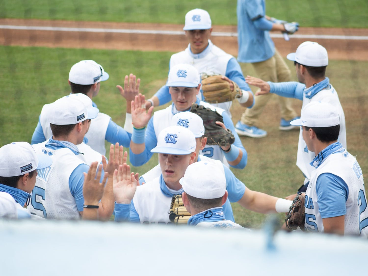 Tar Heel players get high fives from their teammates after a successful inning against University of Virginia at Boshamer Stadium on Saturday, Feb. 27, 2021. The Tar Heels won 2-1.