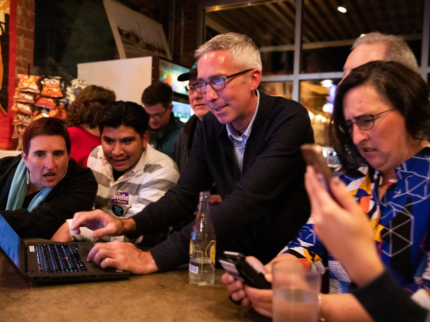 (From left) Allison De Marco, 45, Eliazar Posada, 27, alderman candidate Damon Seils and Molly De Marco, 45, watch local election results during an election party organized by Seils' campaign at Steel String Brewery in Carrboro on Tuesday, Nov. 5, 2019.