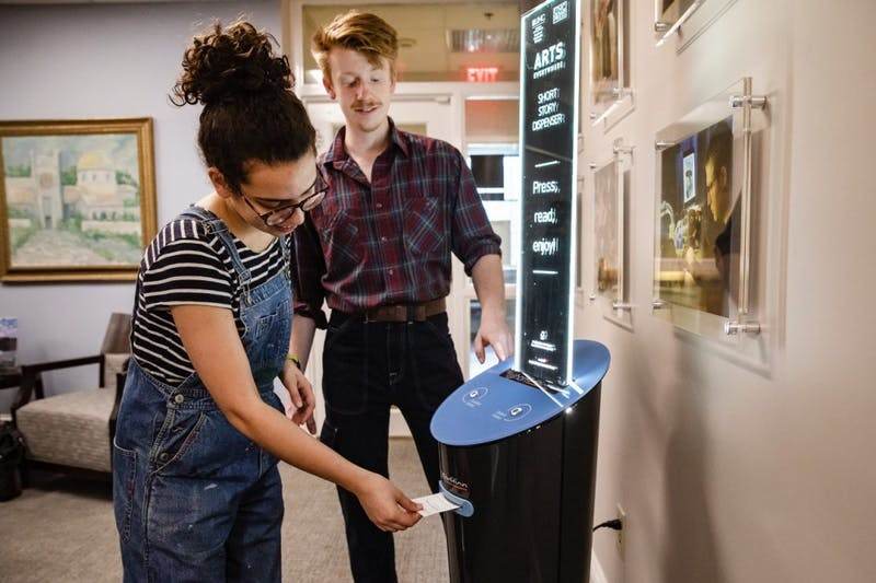 Seniors Ellie Rodriguez and Hampton Smith use the new Short Story Dispenser coming to UNC's campus this week.  Photo courtesy of Johnny Andrews, UNC-Chapel Hill
