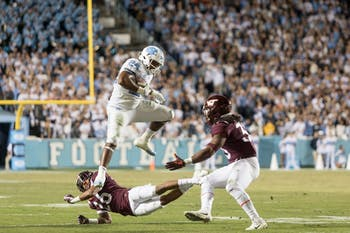 Junior running back Antonio Williams (24) hurdles over an opposing player during the Tar Heels' 22-19 loss against Virginia Tech on the night of Saturday, October 13, 2018 in Keenan Memorial Stadium in Chapel Hill, NC.