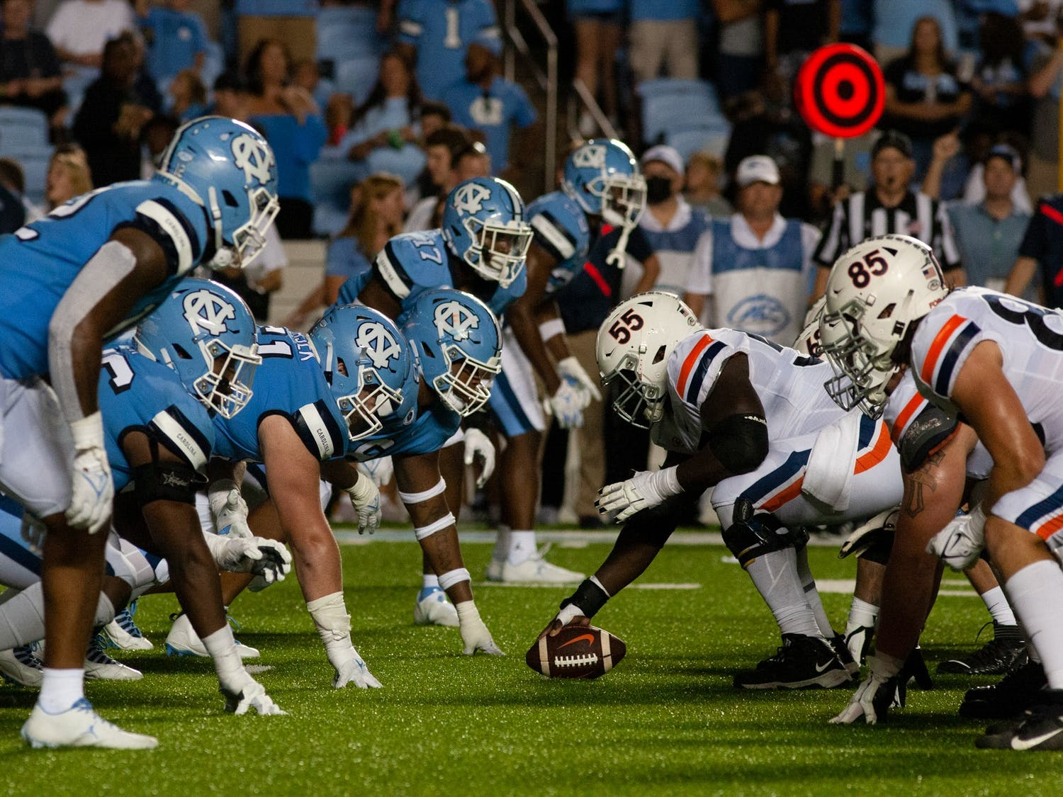 UNC senior center Olusegun Oluwatimi (55) of the University of Virginia prepares to snap the ball. UNC defeated the Cavaliers 59-39, their second win of the season.