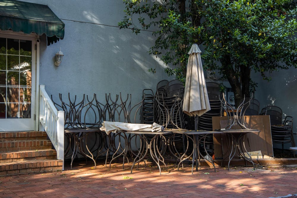 Stacked chairs and picnic tables sit unused in the outdoor eating area of Famous Toastery in Davidson, NC on Thursday, May 14, 2020. Restaurants Restaurants like this and many other businesses across the state are losing business due to the COVID-19 pandemic.