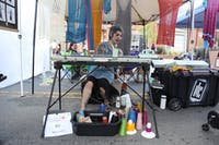 Raleigh-based artist, Eris Swanstrom, knits on a knitting machine at her booth at Festifall, a Chapel Hill festival showcasing local artists. The celebration of art is held annually in Downtown Chapel Hill, this year falling on Sunday. Swanstrom knits on her vintage, special-edition knitting machine as shoppers peruse her racks of skirts, shirts, mittens and other knitted wool garments. Modique Couture, Swanstrom's business, features one-of-a-kind wearable pieces of art. She began knitting 30 years ago, during the process, she discovered knitting machines. Now, Swanstrom sells her work online and at festivals.