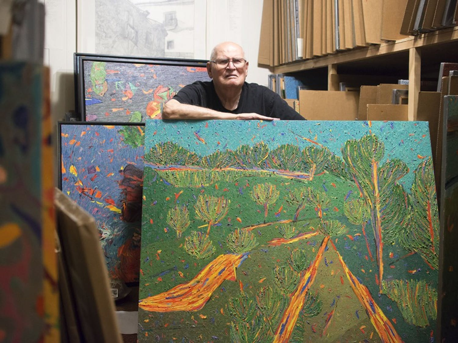 """Marvin Saltzman poses with his artwork in his studio, located in Chapel Hill on July 22nd. A small portion of Saltzman's thousands of pieces is currently on display in the Eno Gallery in Hillsboro. """"I draw from nature, and then I paint about nature.""""""""Bad teachers train, good teachers open doors."""""""