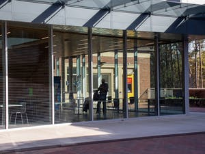 A student walks inside of glass extention to Chase Dining Hall on March 30, 2021.