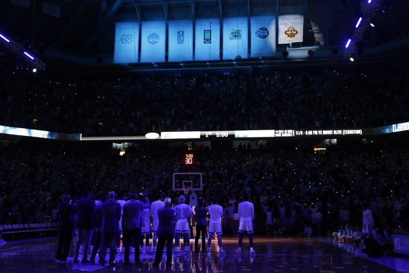 The UNC men's basketball team watches as the 2017 NCAA Men's Basketball National Championship banner is revealed in the Dean Smith Center during Late Night With Roy on Friday night.