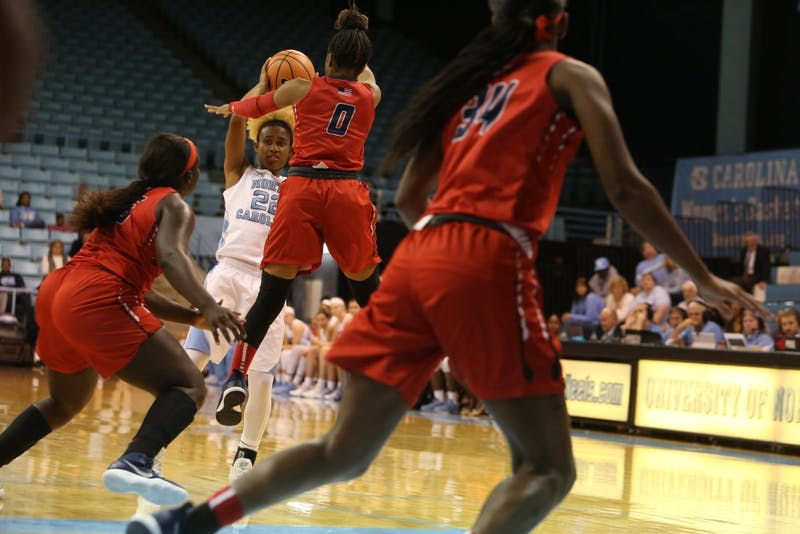 North Carolina junior Paris Kea (22) comes under heavy pressure by South Alabama's Candice Williams (0) during Sunday afternoon's game at Carmichael Arena.