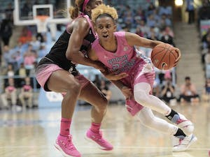 UNC redshirt senior Paris Kea (22) dribbles past an N.C. State defender during her senior night game on Sunday, Feb. 24, 2019. UNC lost the game 74-69.