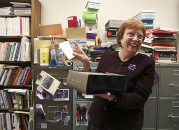 """UNC prof. of English Connie Eble studies linguistics and slang, and is credited with having the earliest documentation of the phrase """"shit happens"""". The phrase was submitted on one of the many notecards which the professor asks her students to submit definitions of current popular slang. Here prof. Eble is posing with the earliest notecard describing """"shit happens""""."""