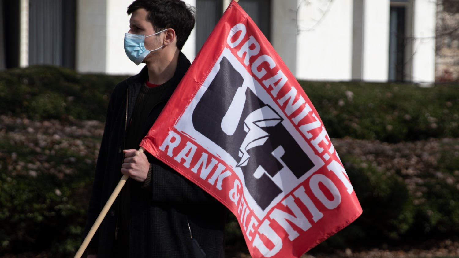 Will Raby, a first-year graduate worker in UNC's department of history, holds a flag at the UE150 rally at the NC legistative builiding, January 14, 2021. UE150 was calling for an improvement to working conditions across the UNC system as the spring semester gets underway.