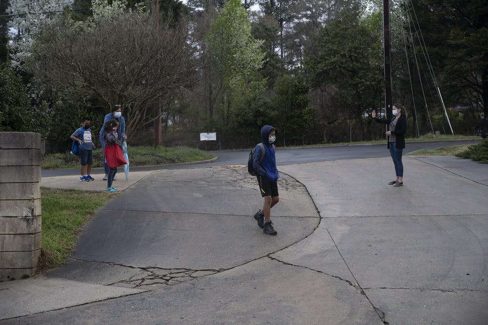 Students of Frank Porter Graham Elementary school walk from carpool toward the school early in the morning on March 26, 2021. CHCCS have recently reopened in-person instruction, although many children are still learning virtually.
