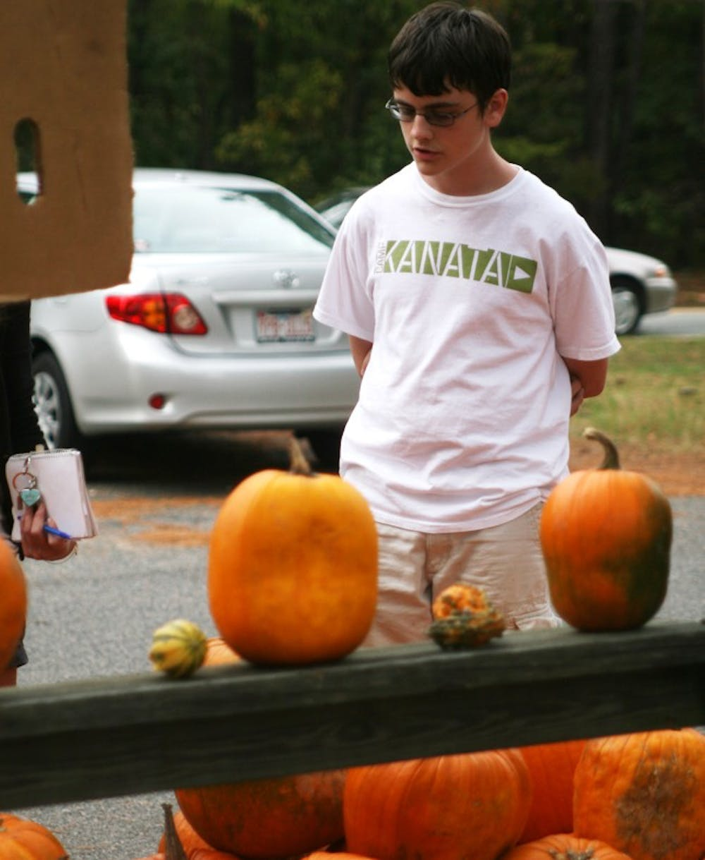 Evan Brown, 14, sells pumpkins at Amity United Methodist Church. The sale is a fundraiser for Brown's church and Boy Scouts troop.