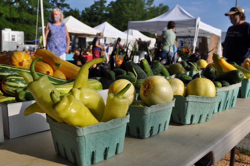 <p>Customers choose from bountiful summer produce from Cate's Corner Farm. All vendors are spaced out 10-20 feet apart, depending where they are in the Market. Photo courtesy of Maggie Funkhouser.</p>