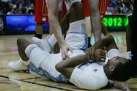 Junior John Henson grabs his wrist after getting injured early in the game. Henson spent most of the night on the bench tending to his wrist, seeing only 7 minutes of play time and scoring only 3 points for the night.